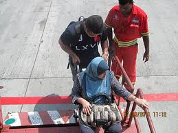 Hoisting a passenger in a wheel chair on Air Asia...risky business