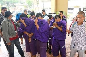 Camera-shy: The Customs officers being led out of the court in Petaling Jaya. (source: The Star)